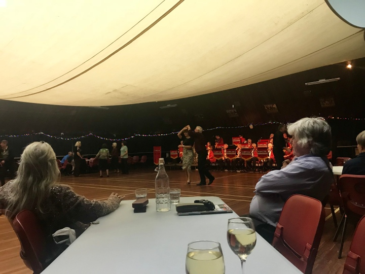 Couple dancing to big band, twirling as spectators take in the scene