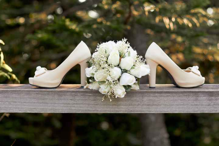 selective focus photography of pair of white open toe chunky heeled shoes and bouquet flowers